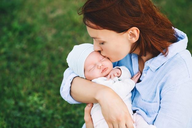 Liebevolle mutter mit ihrem neugeborenen baby auf den armen schöne mutter mit neugeborenem kind in der natur