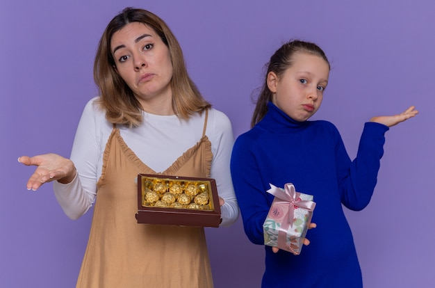 Liebevolle mutter mit schachtel pralinen und tochter, die geschenk hält, das verwirrte arme hebt, die internationalen frauentag feiern, der über lila wand steht