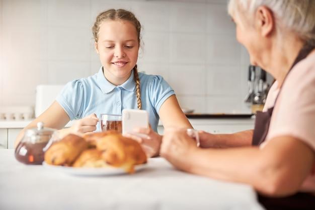 Liebevolle oma und ihre enkelin beim tee zu hause