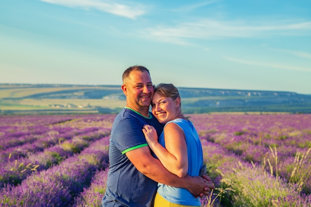 Liebevolle paare auf einem lavendelgebiet bei sonnenuntergang. sonniger sommerabend.