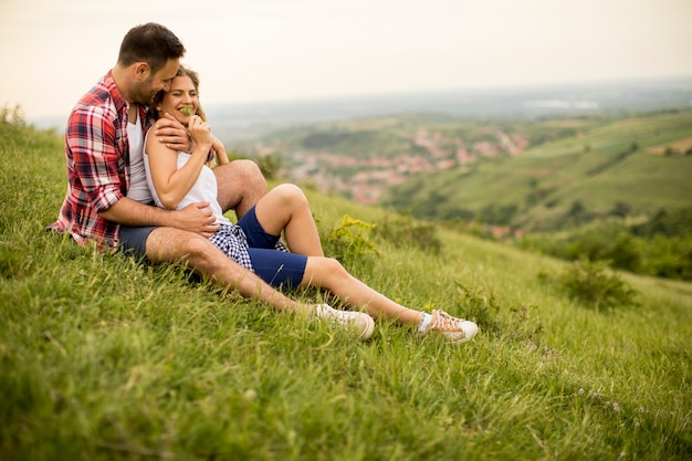 Liebevolle paare, die auf gras im berg umarmt sitzen