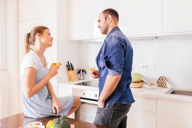 Liebevolle paare, die das weinglas betrachten einander in der küche halten