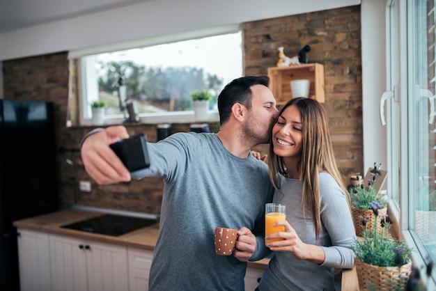 Liebevolle paare, die morgens selfie machen. orangensaft und kaffee in der küche trinken.