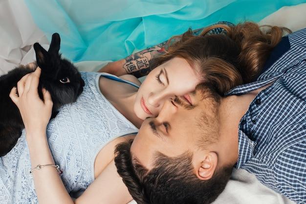 Liebevolle paare, die nahe fenster mit den kaninchenhänden liegen