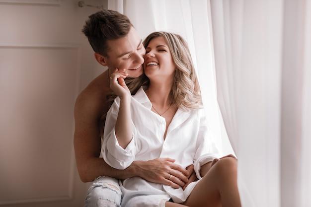 Liebevolle paare, die spaß zusammen zu hause haben, spielerische frau, die lächelndes ehemannohr, -doppelpol, -mann und -frau beißt, die kindisch im bett spielen und lustige vertraute momente genießen