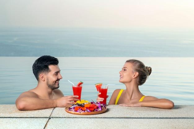 Liebevolle paare schauen sich an, während sie im infinity-pool schwimmen und einen wassermelonen-smoothie trinken