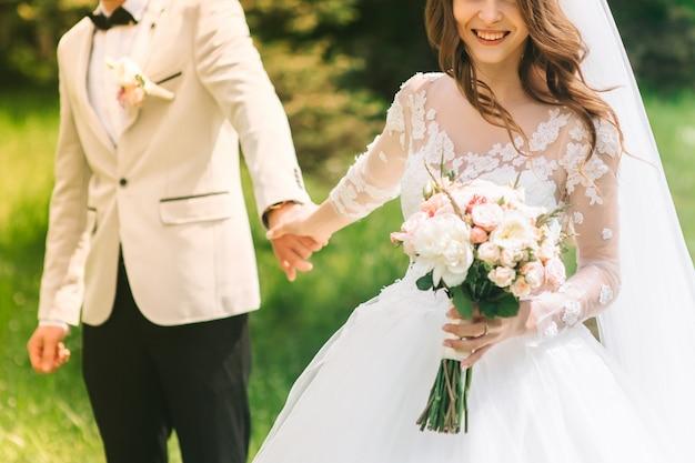 Liebevolle paarhändchenhalten mit ringen gegen hochzeitskleid