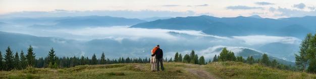 Liebevolle paarwanderer, die auf einem hügel genießt einen morgendunst über den bergen stehen