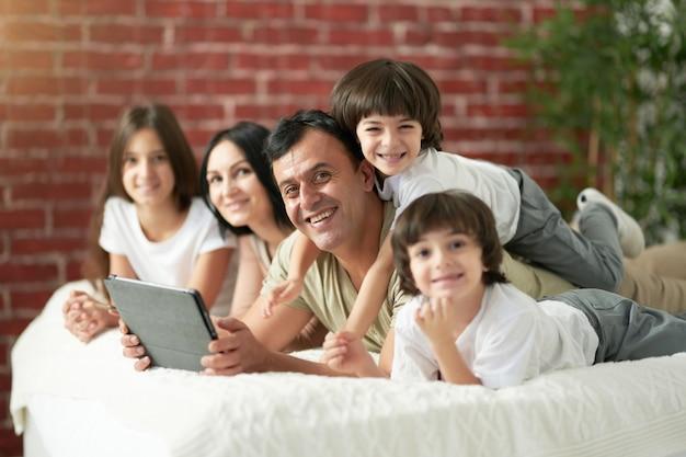 Liebevolle papa-latein-familie mit süßen kleinen kindern, die zeit zusammen zu hause verbringen, wenn vater zuschaut