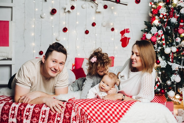 Liebevolle schöne familie in verziertem schlafzimmer an verziertem tannenbaum.