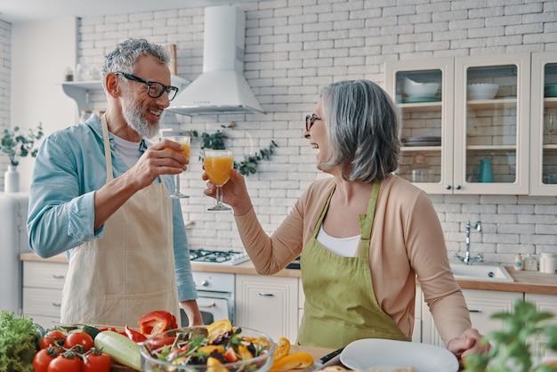 Liebevolle seniorenpaare in schürzen, die sich gegenseitig mit orangensaft anstoßen und ein gesundes abendessen zubereiten, während sie zeit zu hause verbringen