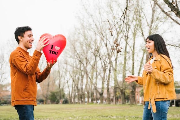 Liebevoller anziehender ballon des glücklichen paars draußen