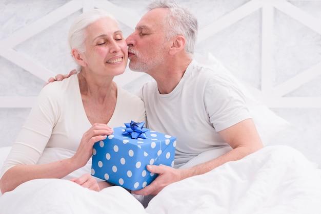 Liebevoller ehemann, der seine frau auf der backe in der hand hält blaue geschenkbox küsst