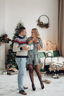 Liebevoller ehemann, der seiner frau weihnachtsgeschenk gibt. schöne frau überrascht durch geschenk vom ehemann.