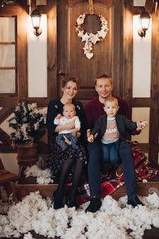 Liebevoller ehemann und ehefrau in voller länge mit zwei kindern auf ihren beinen, die sich unter schneefall küssen, während sie auf einer bank im schneebedeckten innenraum sitzen