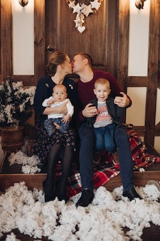 Liebevoller ehemann und ehefrau mit zwei kindern auf ihren beinen, die unter schneefall küssen, während sie auf bank im schneebedeckten innenraum sitzen