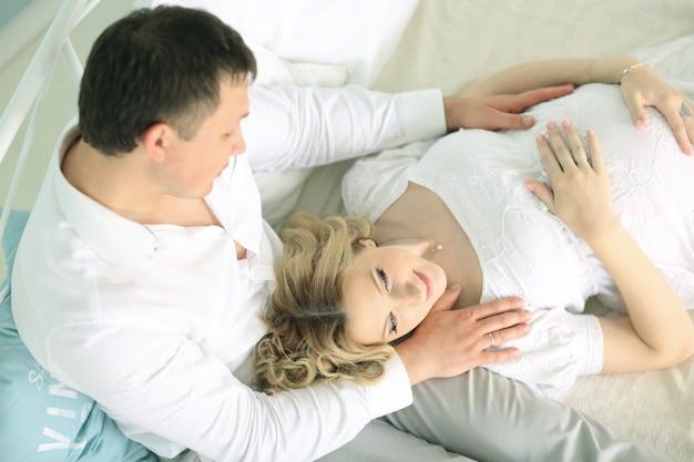 Liebevoller ehemann und seine schwangere frau auf dem bett im schlafzimmer