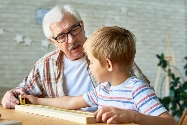 Liebevoller großvater, der enkelhandwerk unterrichtet