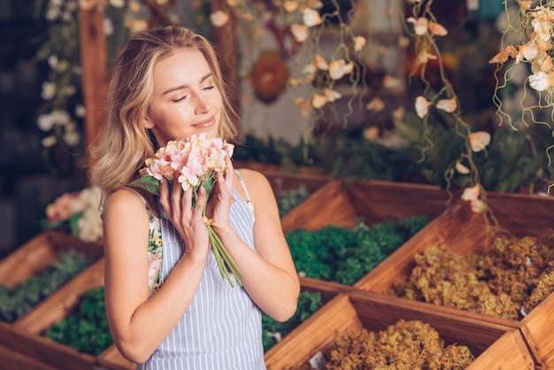 Liebevoller hortensieblumenstrauß des blonden jungen weiblichen floristen, der vor hölzerner kiste steht