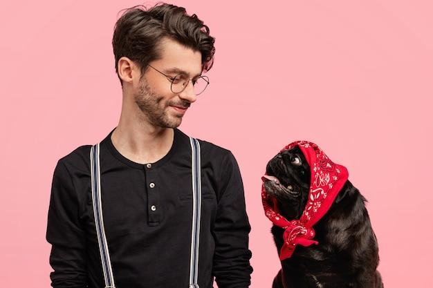 Liebevoller männlicher hundebesitzer schaut mit erfreutem ausdruck und liebe auf sein lustiges haustier mit kopftuch auf dem kopf, fühlt verantwortung, spielt zu hause zusammen, isoliert über rosa wand. stammbaum welpe