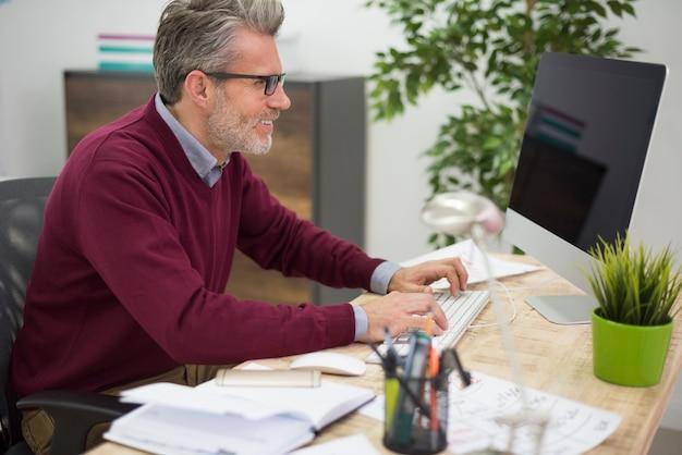 Liebevoller mann, der an seinem computer arbeitet