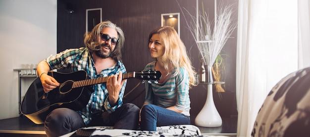 Liebevoller mann, der gitarre für seine frau spielt