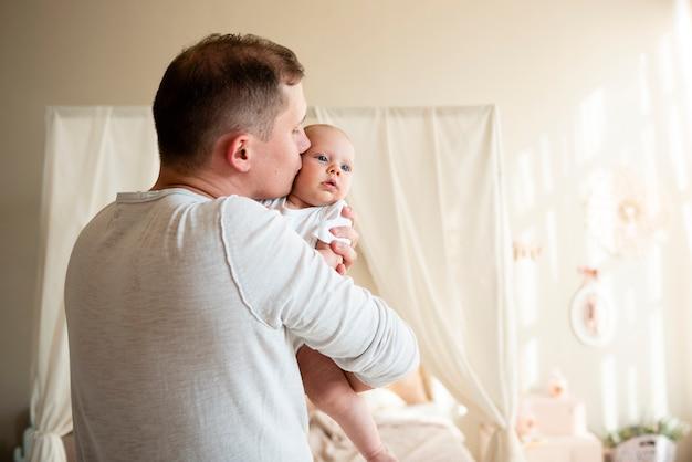 Liebevoller mittlerer schuss des vaters und des babys