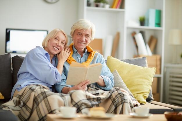 Liebevolles älteres paar, das im gemütlichen raum aufwirft