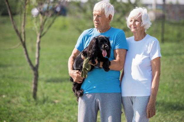 Liebevolles älteres paar mit haustier-hund