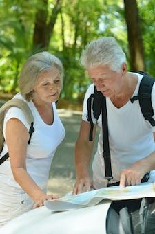 Liebevolles älteres paar mit karte in der nähe von auto im sommer