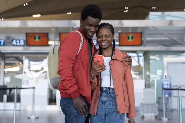Liebevolles afrikanisches reisendespaar, das auf den flug im flughafenterminal wartet und auf das telefon schaut