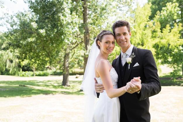 Liebevolles eben verheirateten paartanzen im garten