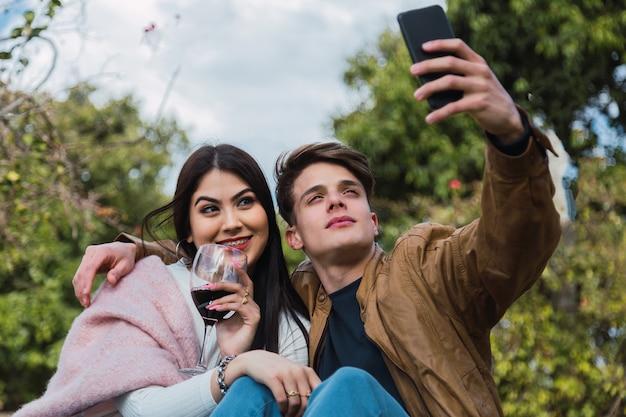 Liebevolles fröhliches glückliches paar, das selfie im garten nimmt