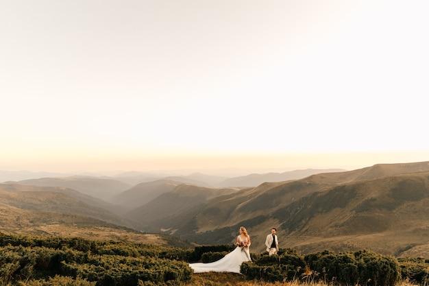 Liebevolles hochzeitspaar, das zärtlich gegen die berge, romantische beziehung, schöne landschaft umarmt.