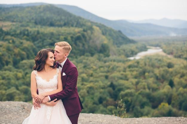 Liebevolles hochzeitspaar in den bergen
