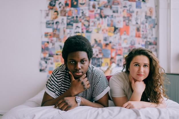Liebevolles interracial-paar, das sich auf weißem bett über 90s stil entspannt