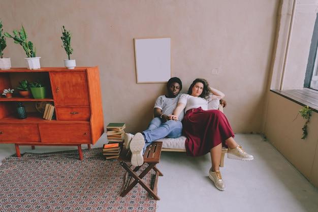 Liebevolles interrassisches paar, das sich im stuhl entspannt