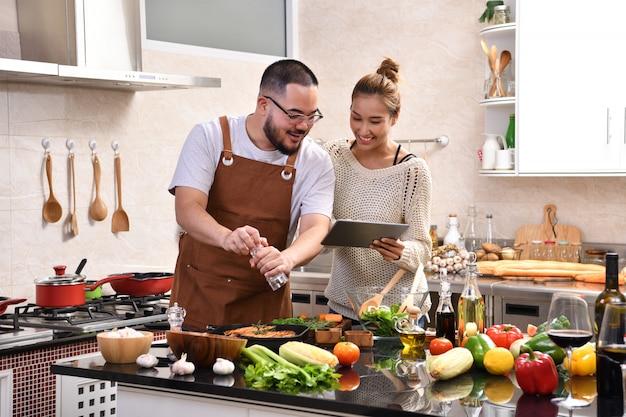Liebevolles junges asiatisches paar, das digitales tablett verwendet und in der küche kocht, die gesundes essen zusammen macht, das spaß fühlt