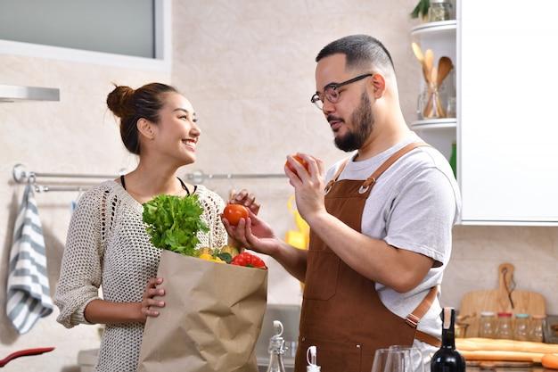 Liebevolles junges asiatisches paar, das in der küche kocht, die gesundes essen macht und einkaufstasche mit gemüse zusammen hält, das spaß fühlt