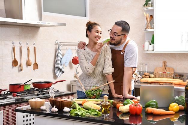 Liebevolles junges asiatisches paar, das in der küche kocht, die gesundes essen zusammen macht, das spaß fühlt