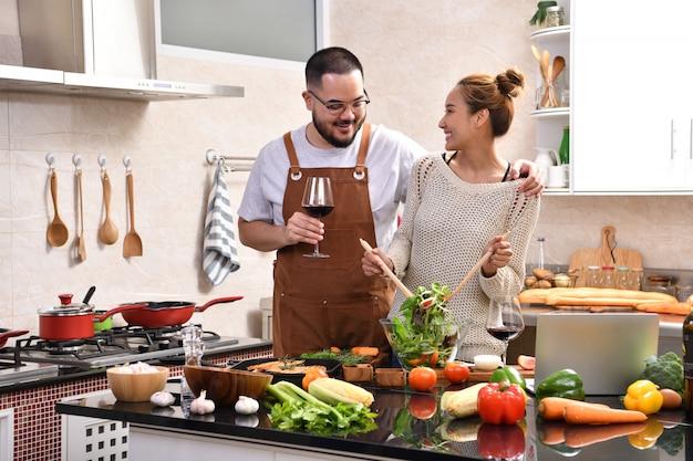 Liebevolles junges asiatisches paar, das in der küche kocht, die zusammen gesundes essen macht und wein trinkt