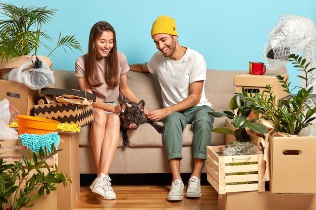 Liebevolles junges paar, das auf der couch sitzt, umgeben von kisten