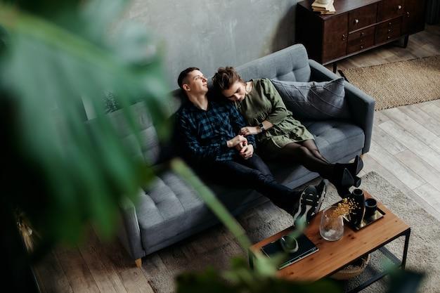 Liebevolles junges paar, das auf einer couch sitzt und kuschelt