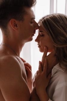 Liebevolles junges paar, das den morgen zu hause nahe dem fenster am valentinstag genießt. mädchen im weißen hemd und halbnackt kerl, der spaß zusammen hat