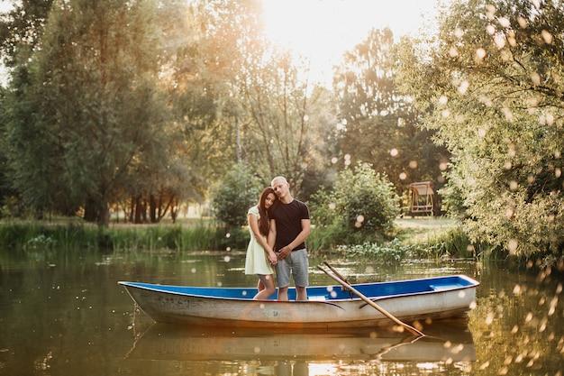 Liebevolles junges paar, das ein boot auf dem see genießt