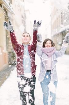 Liebevolles junges paar spielt mit schnee und geht morgens winterstadt