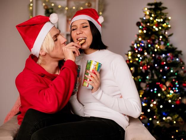 Liebevolles junges paar zu hause zur weihnachtszeit mit weihnachtsmütze im sitzen