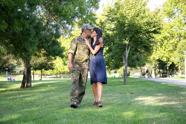 Liebevolles kaukasisches paar, das zusammen auf rasen im park umarmt, küsst und zusammen geht. soldat mittleren alters in militäruniform, der seine hübsche frau umarmt. familientreffen, wochenende und heimkehrkonzept