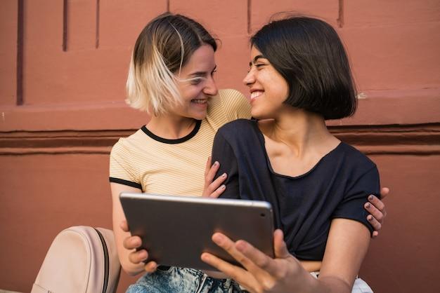 Liebevolles lesbisches paar, das selfie mit digitalem tablett nimmt.