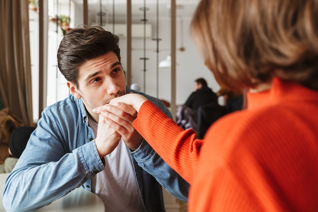 Liebevolles paar, das im restaurant ruht, während hübscher kerl hand seiner brünetten freundin küsst